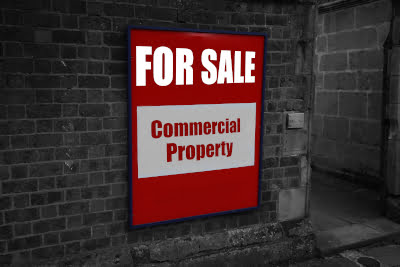 Sign on a building saying Commercial Property for sale indicating a commercial sale
