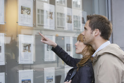 Couple looking at houses in an estate agency window