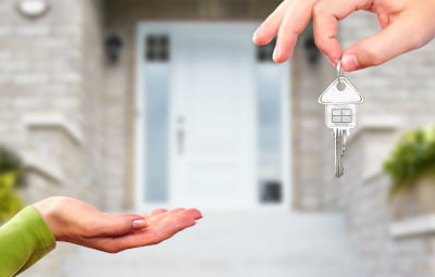 One person handing over keys to another with a house in the background signifying house sale
