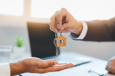 Image of a male hand passing over house keys to a female hand signifying house purchase