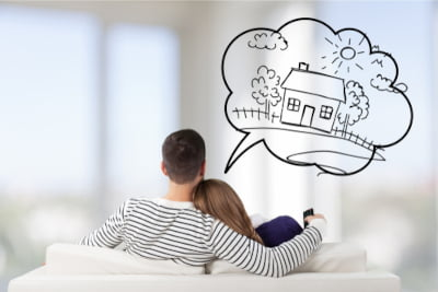 Image of a couple sittling togetehr thinking about their dream house signifying house purchase