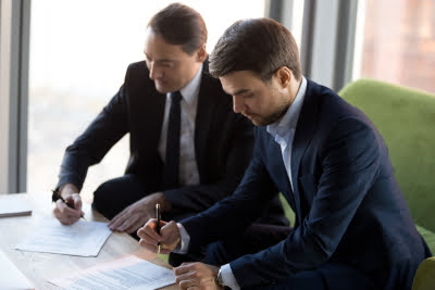 Photo of 2 businessmen signing a partnership agreement