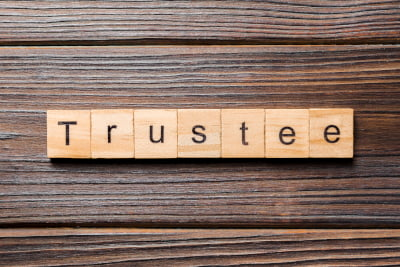 Sign in wooden blocks on a wooden background saying Trustee required in Trusts