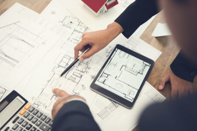 Professional advisers discussing floor plan in a commercial purchase
